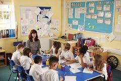 Skolaläraren och ungar arbetar på gruppprojektet, högstämd sikt arkivbild