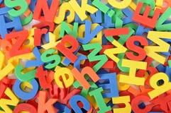 Skolaläsning, handstilbegrepp, bakgrund av plast- leksakalfabetbokstäver Royaltyfri Bild