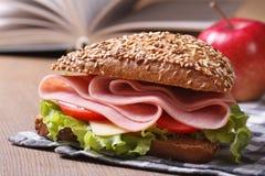 Skolalunch: en skinksmörgås- och äpplecloseup Arkivbild