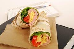 Skolalunch: skinka- och ostsjalsmörgåsen med lunch hänger löst på boken Arkivfoto