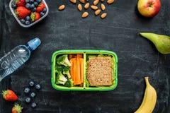 Skolalunchask med smörgåsen, grönsaker, vatten och frukter Arkivbild