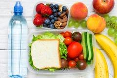 Skolalunchaskar med smörgåsen, nya frukter och grönsaker, bär och muttrar och flaska av vatten Fotografering för Bildbyråer