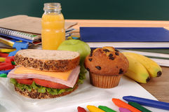 Skolamatsäck, smörgås, äpple, drink på klassrumskrivbordet eller tabell Royaltyfri Foto