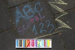 Skolan, abc:et och 123 suckar skriftligt med kulöra chalks på en trottoar Dra tillbaka till skolan på en asfalt och semesterbegre Arkivbild
