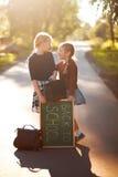 Skolan för två lilla systrar lurar lycklig baksida till skolan Arkivfoto