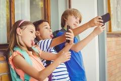 Skolan lurar att ta selfie med mobiltelefonen i korridor arkivfoto