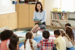 Skolan lurar sammanträde på golvet som lyssnar till den lästa läraren royaltyfria bilder