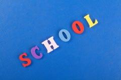 SKOLAord på blå bakgrund som komponeras från träbokstäver för färgrikt abc-alfabetkvarter, kopieringsutrymme för annonstext Arkivfoto