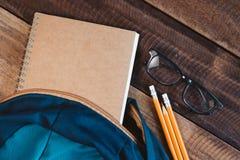 Skolapåse, anteckningsbok, blyertspenna, penna och glasögon på en trätabell royaltyfri fotografi