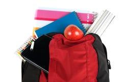 Skolapåse med anteckningsböcker, blyertspennor, minnestavlan, linjalen och äpplet Arkivbild