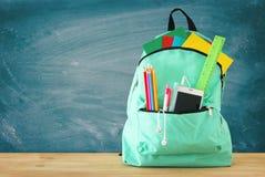 Skolapåse med brevpapper och anteckningsböcker framme av svart tavla tillbaka begreppsskola till arkivfoto