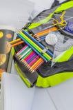 Skolapåsen, ryggsäcken, blyertspennor, pennor, radergummit, skolan, ferie, linjaler, kunskap, bokar Arkivfoton