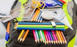 Skolapåsen, ryggsäcken, blyertspennor, pennor, radergummit, skolan, ferie, linjaler, kunskap, bokar Arkivbild