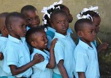 Skolapojkar och flickor skynda sig grupp för köen upp till i Robillard, Haiti Arkivfoton