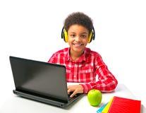 Skolapojke med hörlurar med mikrofon och bärbara datorn Arkivfoton