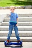 Skolapojke på blå hoverboard Arkivfoto