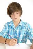 Skolapojke som arbetar med en blyertspenna som isoleras på vit Fotografering för Bildbyråer