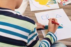 Skolapojke som drar geometriska former på papper med blyertspennan Unge läxa, utbildningsbegrepp Royaltyfria Bilder