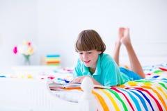 Skolapojke som läser en bok i säng Fotografering för Bildbyråer
