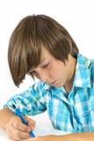 Skolapojken med blyertspennan arbetar koncentrerat, isolerat på vit Royaltyfri Foto