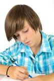 Skolapojken med blyertspennan arbetar koncentrerat, isolerat på vit Arkivfoto