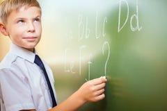 Skolapojken skriver engelskt alfabet med krita på svart tavla Arkivbilder