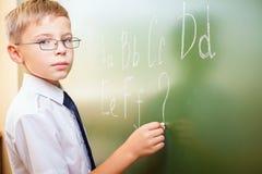 Skolapojken skriver engelskt alfabet med krita på svart tavla Fotografering för Bildbyråer
