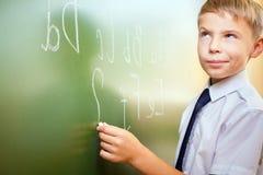 Skolapojken skriver engelskt alfabet med krita på svart tavla Arkivbild
