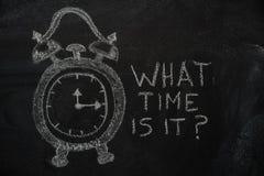 Skolaringklockan och vilken tid är det? text på den svarta svart tavlan royaltyfria foton