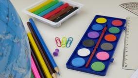 Skolaskrivbord med olika färgrika tillförsel Tillbaka till skolabegreppet arkivfilmer