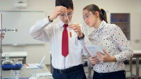 Skolastudenter som arbetar på en kemi, projekterar tillsammans i kemiklassrum lager videofilmer