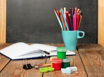 Skolatillförsel, öppen anteckningsbok och svart tavla Arkivbild