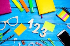 Skolatillförsel i skolaskrivbordet, brevpapper, skolabegrepp, blå bakgrund, idérikt kaos, utrymme för text, markörer, pennor, int arkivfoton