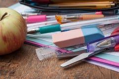 skolatillförsel och äpple på träskrivbordbakgrund Royaltyfri Bild