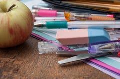 skolatillförsel och äpple på träskrivbordbakgrund Royaltyfria Bilder