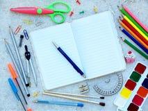 Skolatillförsel och den öppna anteckningsboken med pennöverkanten gränsar Arkivfoto