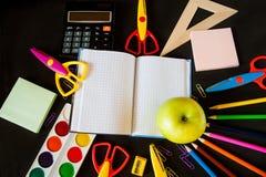 Skolatillförsel och ett stort grönt äpple på notepaden i mitten Fotografering för Bildbyråer