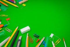 Skolatillförsel på den gröna svart tavlan tillbaka till skolabakgrund Arkivbild