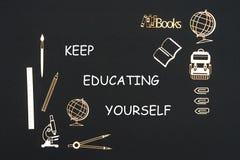 Skolatillförsel som förläggas på svart bakgrund med text, håller att utbilda sig arkivbild
