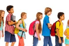 Skolaungar går i överensstämmelse med ryggsäckprofilsikt arkivfoton
