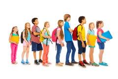 Skolaungar med ryggsäckar och läroböcker arkivbild