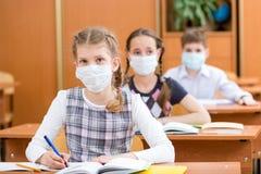 Skolaungar med skyddsmaskeringen mot influensavirus Arkivfoto
