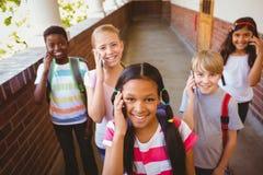 Skolaungar som använder mobiltelefoner i skolakorridor Arkivfoto