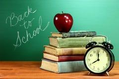 Skolböcker, Apple och klocka på skrivbordet på skolan Arkivbild