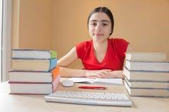 Skolböcker på skrivbordet, utbildningsbegrepp flicka som hemma gör kurser Fotografering för Bildbyråer