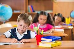 Skolbarn i klassrum på skolan fotografering för bildbyråer