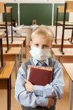 Skolbarn i medicinsk framsidamaskering royaltyfria bilder