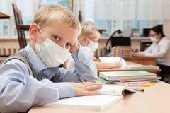 Skolbarn i medicinsk framsidamaskering arkivfoton