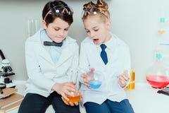 Skolbarn i vita lag som rymmer agens, i att sitta för flaskor Royaltyfri Bild
