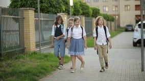 Skolbarn med ryggsäckar i solnedgångljus som hem kommer från skola tillbaka ungeskola till lager videofilmer